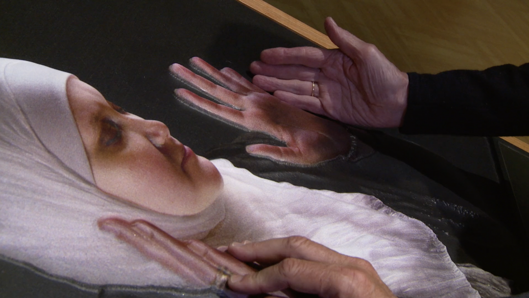 Woman touching a tactile image.